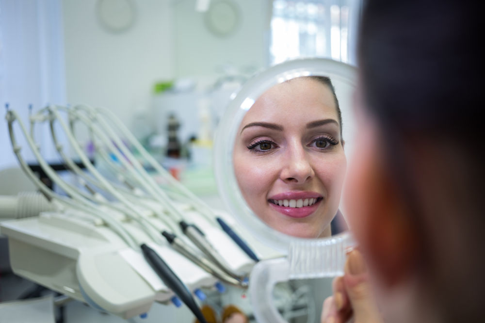dental emergency south windsor - patient-looking-at-her-face-in-mirror (1)